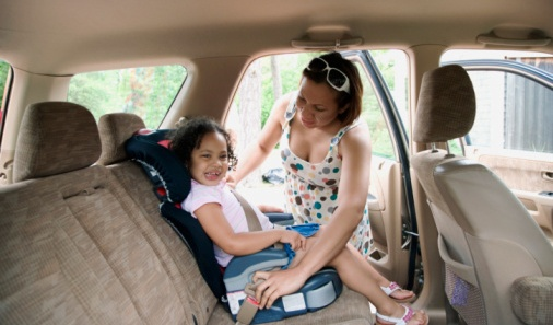 Mother-putting-daughter-in-car-seat