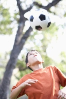 Young boy heading soccer ball