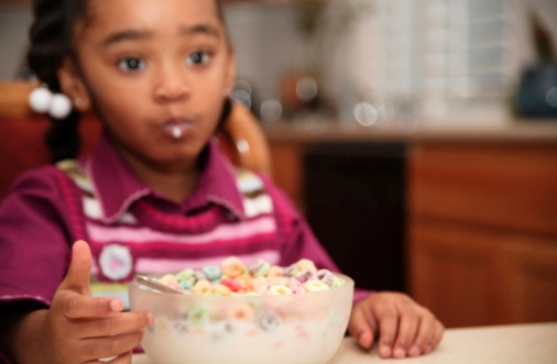 Young Girl Eating Cereal For Breakfast