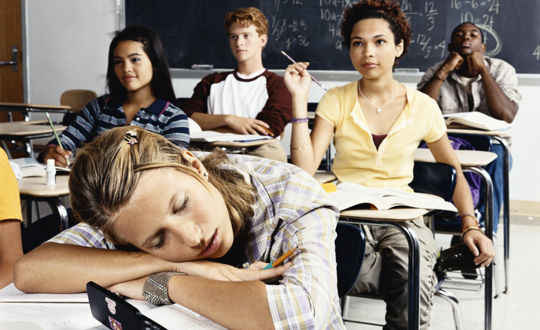 Teenager sleeping in classroom at desk